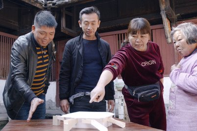 Mr John Lin (second from left) discussing the design options of renovating Tulou with the local residents