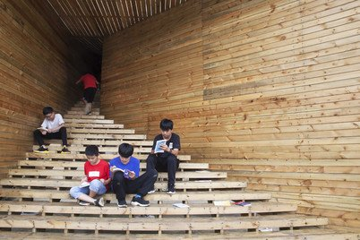 Children gathering at the sheltered steps of the 'Plug-in' which connects to the book corner of Tulou