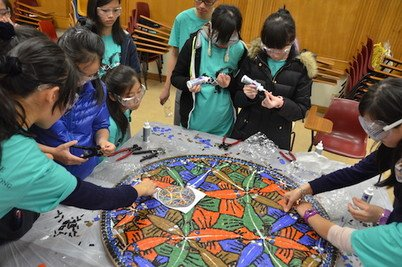 Participants assembling the woodcut Circle Limit III by M.C. Escher using mosaic tiles