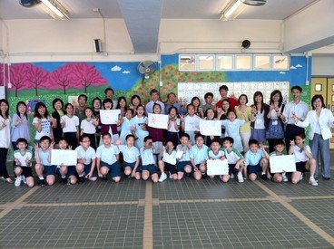 Primary school participants (front) showing their artworks at the end of the orientation day with their mentors (back)